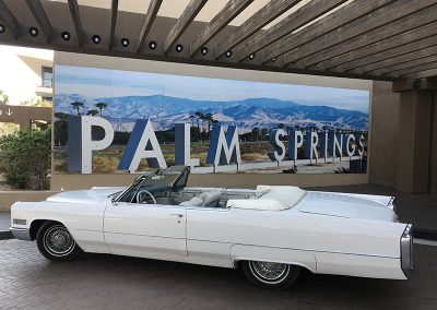White 1966 Cadillac DeVille Convertible in front of Palm Springs Sign